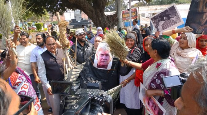 Women Survivors Flay US President Trump in Effigy with Brooms on Occasion of his Visit to India